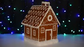 The hand-made eatable gingerbread house, snow decoration. Garland background illumination stock video
