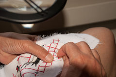 Hand-made embroidery. Woman's hands skillfully embroider on canvas Royalty Free Stock Photo
