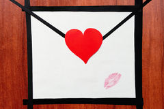 Hand made envelope with heart and lipstick kiss on the wooden ta Royalty Free Stock Photography