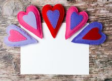 Hand made felt colorful hearts white paper on wooden background. Hand made felt colorful hearts and white paper on wooden background. Concept for congratulation Royalty Free Stock Photography