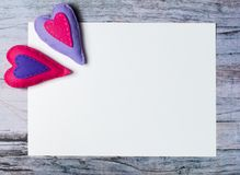 Hand made felt colorful hearts white paper on wooden background. Hand made felt colorful hearts and white paper on wooden background. Concept for congratulation Stock Photo
