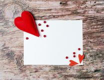 Hand made felt colorful hearts white paper on wooden background. Hand made felt colorful hearts and white paper on wooden background. Concept for congratulation Stock Images