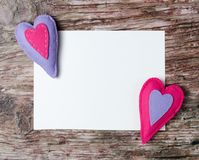 Hand made felt colorful hearts white paper on wooden background. Hand made felt colorful hearts and white paper on wooden background. Concept for congratulation Royalty Free Stock Images