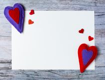 Hand made felt colorful hearts white paper on wooden background. Hand made felt colorful hearts and white paper on wooden background. Concept for congratulation Royalty Free Stock Photos