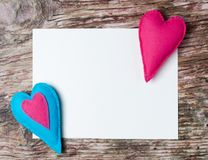 Hand made felt colorful hearts white paper on wooden background. Hand made felt colorful hearts and white paper on wooden background. Concept for congratulation Stock Photos