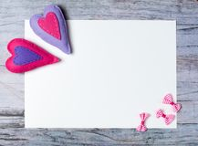 Hand made felt colorful hearts white paper on wooden background. Hand made felt colorful hearts and white paper on wooden background. Concept for congratulation Stock Photography