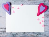Hand made felt colorful hearts white paper on wooden background. Hand made felt colorful hearts and white paper on wooden background. Concept for congratulation Stock Image