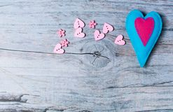 Hand made felt colorful hearts on wooden background. Concept for congratulation, inviting, wedding banner, flyer. Craft element for Valentine`s Day, romantic Stock Photos