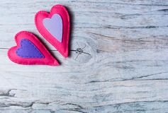 Hand made felt colorful hearts on wooden background. Concept for congratulation, inviting, wedding banner, flyer. Craft element for Valentine`s Day, romantic Stock Photo