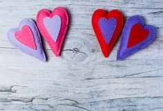 Hand made felt colorful hearts on wooden background. Concept for congratulation, inviting, wedding banner, flyer. Craft element for Valentine`s Day, romantic Stock Photography