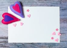 Hand made felt hearts decorations white paper on wooden background. Hand made felt hearts, decorations and white paper on wooden background. Concept for Royalty Free Stock Photos