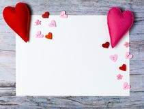 Hand made felt hearts decorations white paper on wooden background. Hand made felt hearts, decorations and white paper on wooden background. Concept for Royalty Free Stock Image