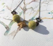 Felt wool Necklace. Hand Made from Felt Wool Felt Necklace with volcanic rock on a hand painted watercolour background Stock Photo