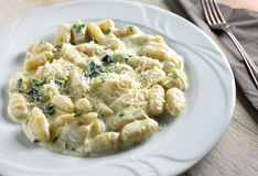 Hand made gnocchi and fork on a wood background.  stock photos