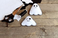 Hand made Halloween ghosts ornaments. Two little felt ghosts, felt scraps, scissors, thread, needle on an old wooden background Stock Photos
