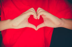 Hand made heart shape on a rad background Stock Photo