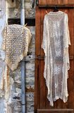 Hand made laces and needlework hang on shop wall, village Pano L Royalty Free Stock Photo