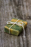Hand made organic soap. Freshly made organic bar of lemongrass soap on an old wooden table royalty free stock photography