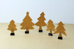 Hand made paper Christmas trees with binder clip. On brown paper background Stock Photos