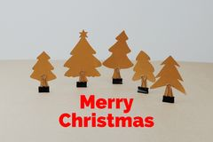 Hand made paper Christmas trees with binder clip and words. `Merry Christmas` on brown paper background Royalty Free Stock Photo