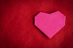 Hand made paper heart on red paper as background. Stock Photos