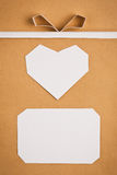 Hand made paper tag and heart on kraft paper as background. Stock Image