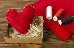 Hand made red felt heart, thread, cloth on wooden background royalty free stock photos