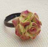 Flower Rose Ring. Hand made ring in a shape of a rose from polymer clay on textured background Royalty Free Stock Photography