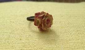 Flower Rose Ring. Hand made ring in a shape of a rose from polymer clay on textured yellow background Stock Images