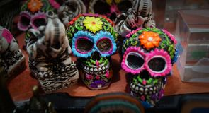 Hand made skulls. Couple of skulls made of baked clay, hand painted decorative pieces of two skulls hand painted in bright colors as blue, pink and green over a stock photography