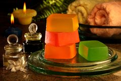 Hand made soaps with perfumes. Display of handmade soaps, towel and perfume oils with candle light Royalty Free Stock Photos