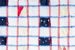 Textile pattern of square pieces of colored fabrics, sewn by red and blue zigzag seams on white fabric. Hand-made textile pattern of square pieces of colored Royalty Free Stock Photo
