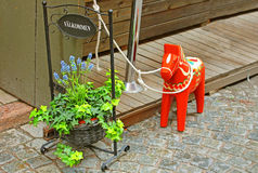 Hand-made traditional wooden Dalecarlian Horse (symbol of Swedish Dalarna and Sweden in general). Inscription Welcome, flowers and a hand-made traditional wooden Royalty Free Stock Photography
