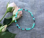 Hand Made Turquoise bracelet. On a linen background with rose flowers Stock Image