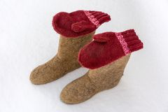 Hand-made valenki and mittens on white snow. Traditional Russian clothes and shoes in the winter royalty free stock image