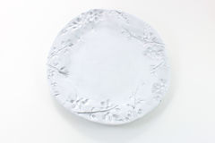 Hand made white plate with the imprint of twigs and berrie. S, isolated on white stock photo