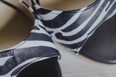 Hand-made womens dance shoes made of genuine leather on the wooden surface. Macro photography. black and white as a zebra style. from the top view Royalty Free Stock Photography