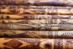 Hand made wooden bamboo carving engraved fish figure artwork on bamboo, rows of engraved bamboo sticks. textured background. triba Royalty Free Stock Photography