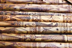 Hand made wooden bamboo carving engraved fish figure artwork on bamboo, rows of engraved bamboo sticks. textured background. triba Royalty Free Stock Image