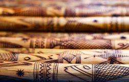 Hand made wooden bamboo carving engraved fish figure artwork on bamboo, rows of engraved bamboo sticks. textured background. triba Royalty Free Stock Photo