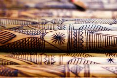 Hand made wooden bamboo carving engraved fish figure artwork on bamboo, rows of engraved bamboo sticks. textured background. triba Stock Photos