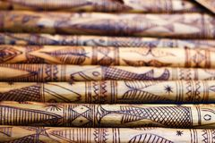 Hand made wooden bamboo carving engraved fish figure artwork on bamboo, rows of engraved bamboo sticks. textured background. triba Stock Photo