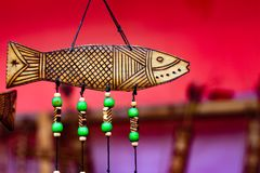 Hand made wooden carving engraved fish figure artwork on wood plank with suspended green beads on string.tribal artwork. textured Royalty Free Stock Image