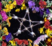Hand made wooden pentagram in circle of flowers, top view Royalty Free Stock Photography
