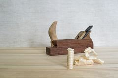 Hand-made wooden plane and wooden shavings on the table close-up. The concept of DIY. Tools for woodworking and crafts. stock images