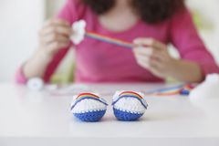 Hand made woolen bootees with a colorful rainbow Stock Image