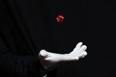 Hand of magician in white glove showing tricks with dice. Hand of man magician in white glove showing tricks with dice flying in the air over black background Royalty Free Stock Photo