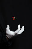 Hand of magician in white glove showing tricks with dice Stock Image