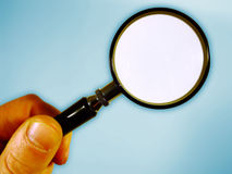 Hand and magnifying glass. A hand holds a small magnifying glass against a light blue background. Area magnified by the glass is clear and white stock photography