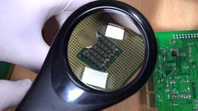 Hand with magnifying glass examining computer cpu processor stock video footage
